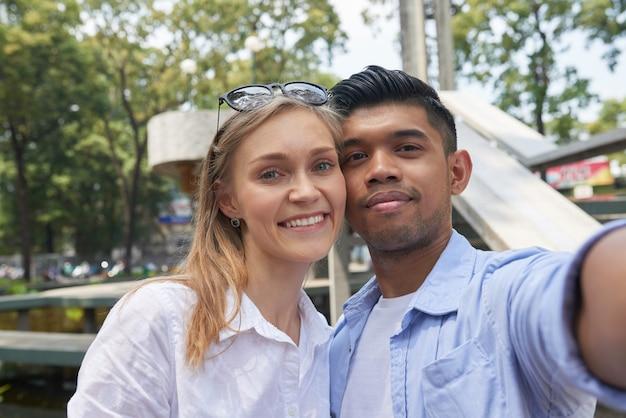 Fröhlich lächelndes, vielfältiges paar, das beim spaziergang in der stadt, in die sie gereist sind, ein selfie auf dem smartphone macht