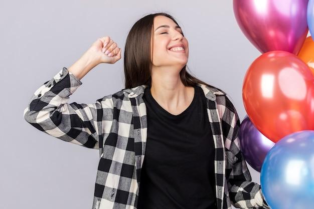 Fröhlich mit geschlossenen augen junges schönes mädchen, das in der nähe ballons steht und die ja-geste einzeln auf weißer wand zeigt
