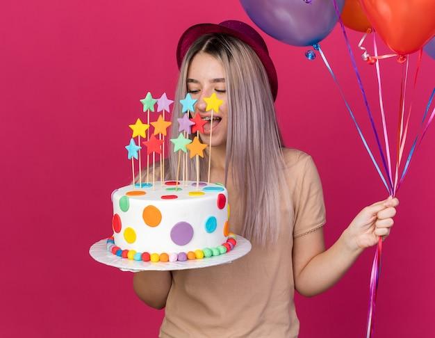 Fröhlich mit geschlossenen augen junges schönes mädchen mit partyhut, das luftballons mit kuchen hält