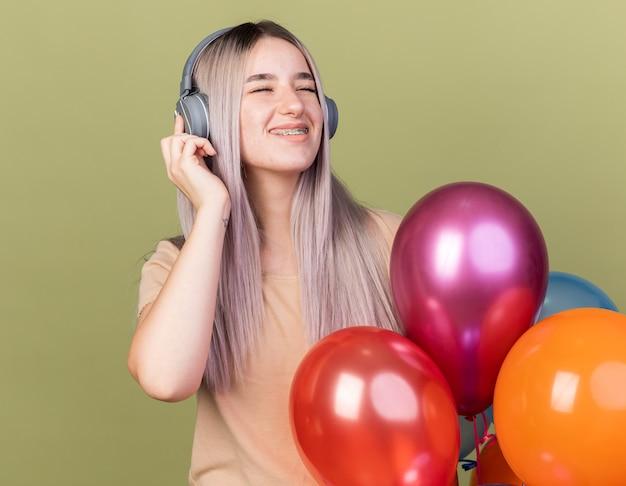 Fröhlich mit geschlossenen augen junges schönes mädchen mit zahnspangen und kopfhörern, die in der nähe von ballons stehen