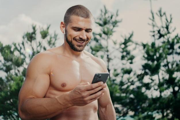 Fröhlich motivierter hemdloser sportler, der sich auf das smartphone konzentriert, sendet textnachrichten