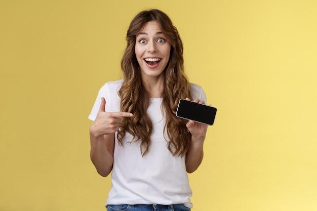 Fröhlich überrascht süßes glückliches mädchen schlug beste punktzahl tolles spiel, das smartphone-display zeigt, das mit dem zeigefinger auf den horizontalen bildschirm des mobiltelefons zeigt, führen eine coole app ein, die auf breitem gelbem hintergrund lächelt
