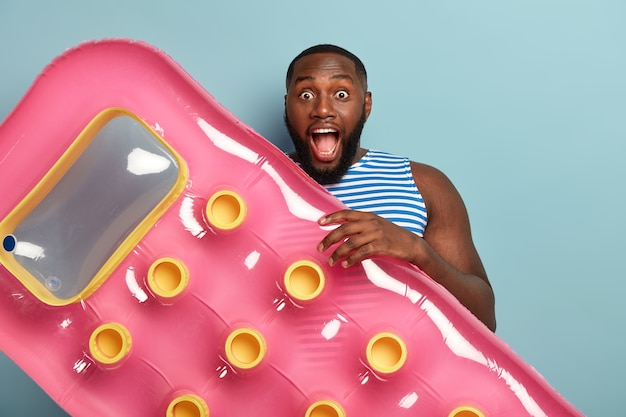 Fröhlich überraschter mann mit muskulösem körper, hält rosa aufblasbare schwimmmatratze, geht auf dem wasser entspannen, ruht im spa-resort