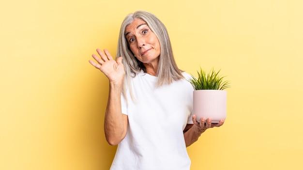 Fröhlich und fröhlich lächeln, mit der hand winken, begrüßen und begrüßen oder sich mit einer zierpflanze verabschieden