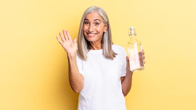 Fröhlich und fröhlich lächeln, mit der hand winken, begrüßen und begrüßen oder sich verabschieden und eine wasserflasche halten