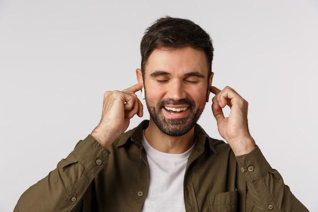 Fröhlich und sorglos, glücklich, gut aussehender bärtiger mann im mantel, nahe augen und entzückt lächelnd, berührende drahtlose ohrhörer in guter klangqualität, lieblingsmusik hören