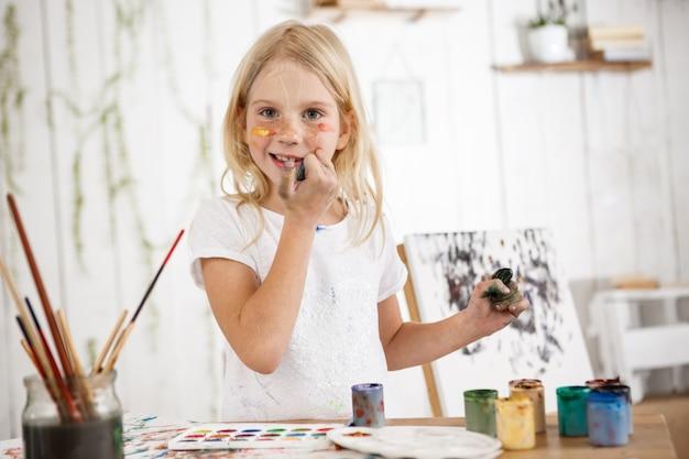 Fröhlich und voller freude, kreative kleine blondine, die lächelt und ihr gesicht mit schmutzigen händen berührt
