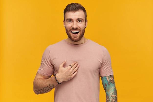 Fröhlich verblüffter tätowierter junger mann im rosa t-shirt mit bart sieht aufgeregt aus und zeigt mit der hand über die gelbe wand auf sich