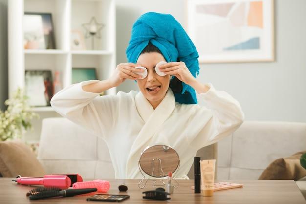 Fröhlich zeigt junges mädchen mit zunge bedeckte augen mit schwamm, die am tisch mit make-up-tools im wohnzimmer sitzen