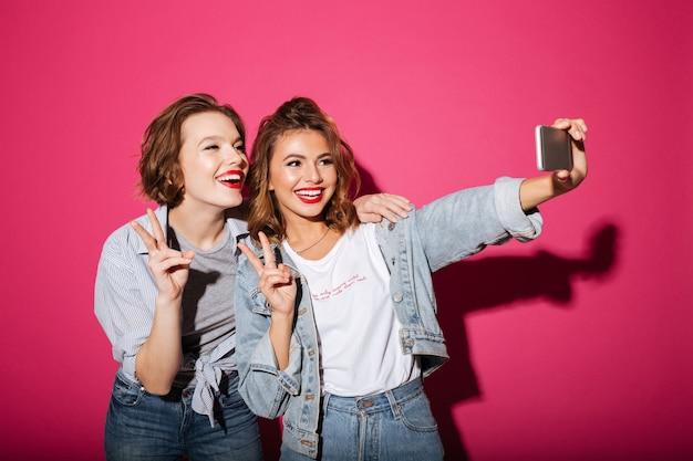Fröhlich zwei frauen machen selfie per telefon