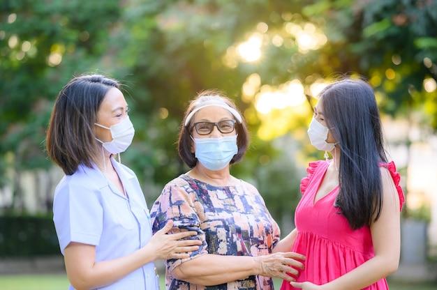 Fröhliche ältere asiatische frau mit pflegekraft und zwei monate schwangere frau mit gesichtsmaske, die eine gute zeit im freien hat konzentriert auf ältere frau