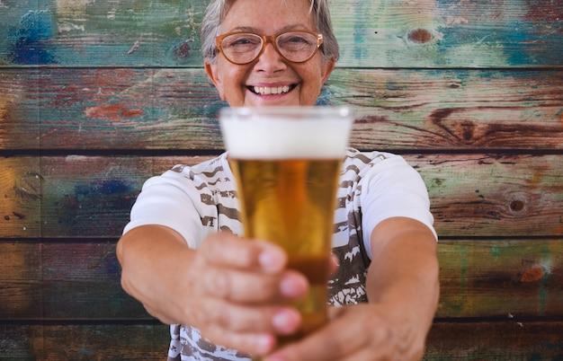 Fröhliche ältere frau, die an einem holztisch sitzt und ein glas blondes bier hält und in die kamera schaut