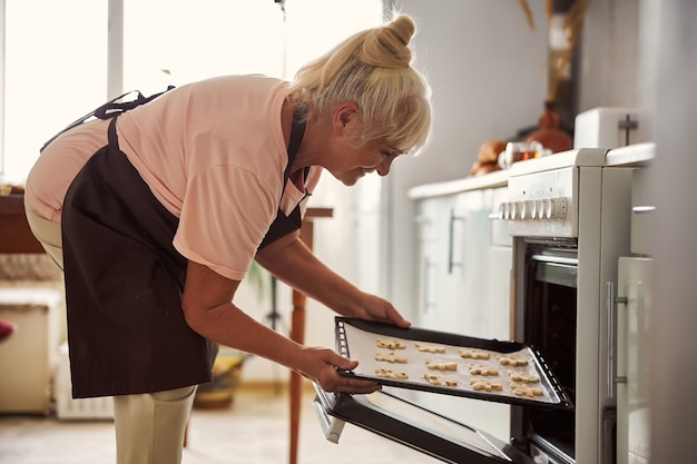 Fröhliche ältere frau, die ein tablett mit keksen in den ofen stellt
