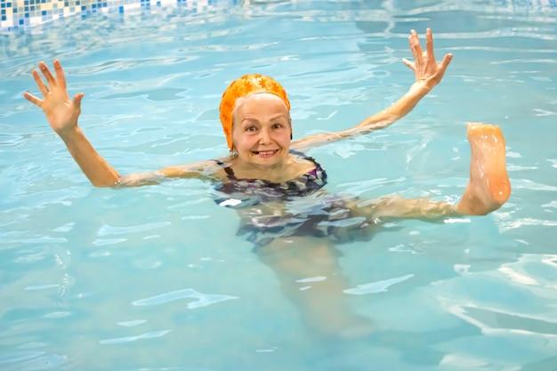 Fröhliche ältere frau in lustiger pose nach aqua-aerobic-kursen im schwimmbad