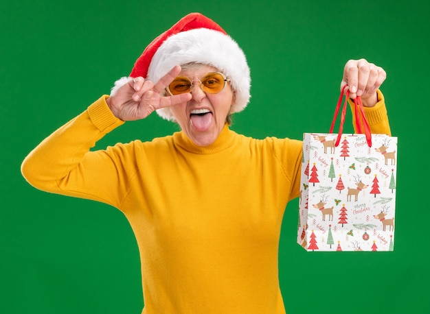 Fröhliche ältere frau in sonnenbrille mit weihnachtsmütze streckt die zunge heraus und hält eine geschenktüte aus papier, die das siegeszeichen einzeln auf grüner wand mit kopienraum gestikuliert