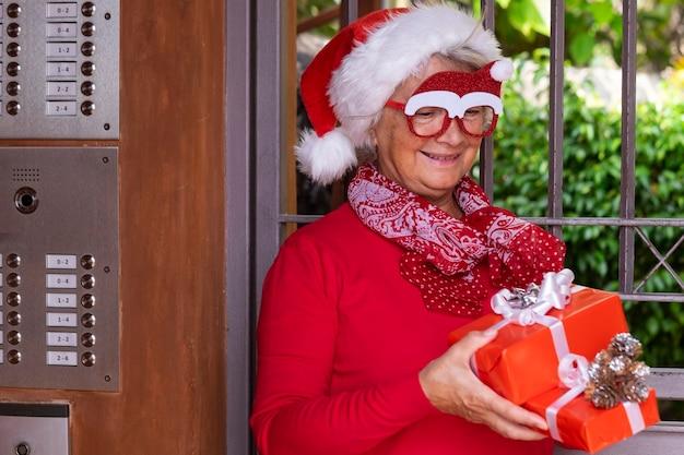 Fröhliche ältere frau mit weihnachtsmütze und lustiger brille, die an der haustür wartet, um weihnachtsgeschenke zu liefern
