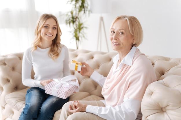 Fröhliche ältere frau verteilt eine kleine geschenkbox an ihre charmante tochter, die eine größere geschenkbox auf ihrem schoß hält, während beide nach vorne schauen und lächeln