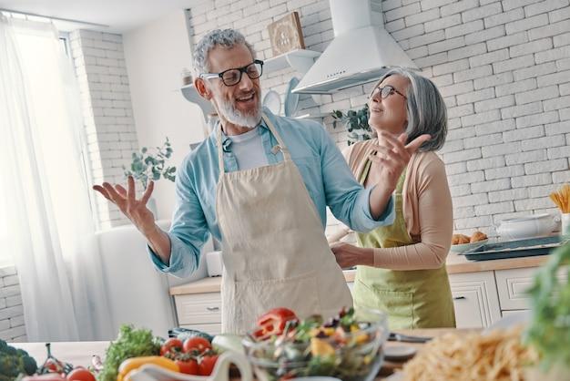 Fröhliche ältere paare, die sich darauf vorbereiten, ein abendessen zu kochen und zu lächeln, während sie zeit zu hause verbringen