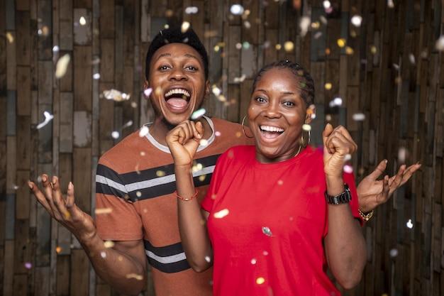 Fröhliche afrikaner feiern mit konfetti vor einer holzwand