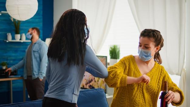 Fröhliche afrikanerin und ihre freundin berühren den ellbogen und halten soziale distanz, während sie sich gegenseitig mit gesichtsmaske grüßen, um die ausbreitung des coronavirus im zuge der globalen pandemie im wohnzimmer zu verhindern