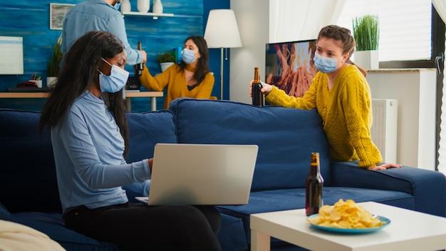 Fröhliche afrikanische frau, die einem freund, der im wohnzimmer sitzt, ein video auf dem laptop zeigt und aufgrund der coronavirus-pandemie soziale distanz hält, um die ausbreitung des virus zu verhindern. menschen, die während des covid-19-ausbruchs kontakte knüpfen