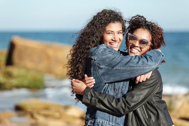 Fröhliche afrikanische freundinnen, die draußen am strand gehen.