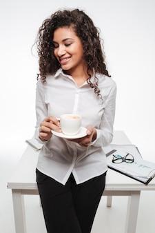 Fröhliche afrikanische geschäftsfrau, die gläser trägt, die kaffee trinken