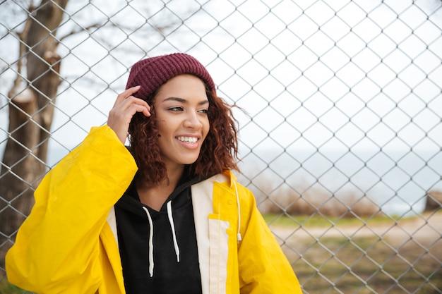 Fröhliche afrikanische junge dame, die draußen geht