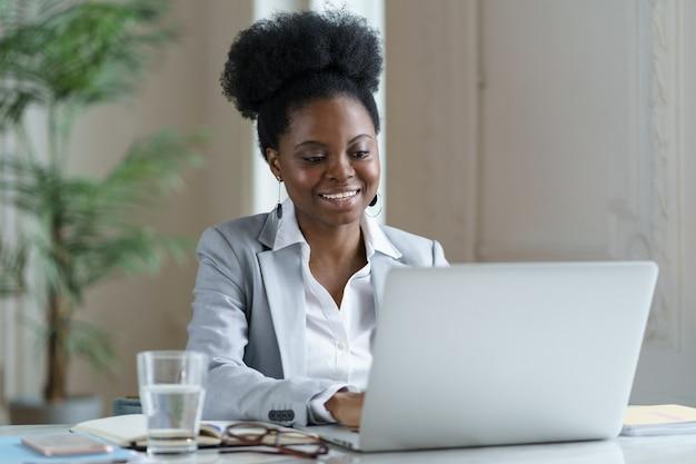Fröhliche afro-geschäftsfrau schaut auf laptop mit positivem lächeln beim lesen von e-mails mit erfolgreichen guten nachrichten