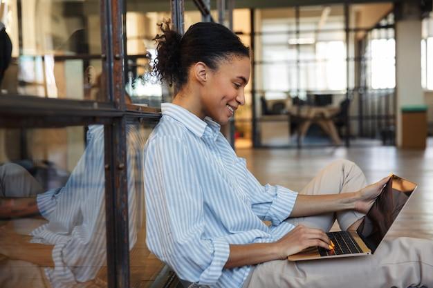 Fröhliche afroamerikanerin lächelt und tippt auf dem laptop, während sie in einem modernen büro auf dem boden sitzt