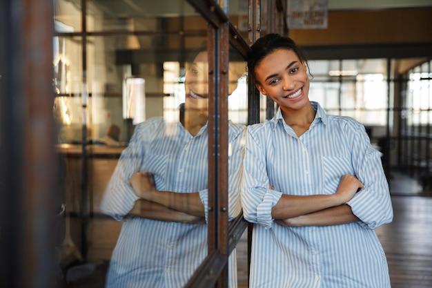 Fröhliche afroamerikanerin mit gekreuzten händen lächelnd, während sie sich in einem modernen büro an eine glaswand lehnt