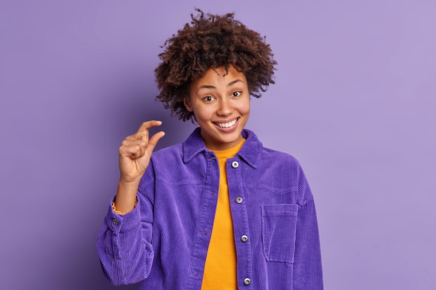 Fröhliche afroamerikanerin mit lockigem haar zeigt kleine stände, die fröhlich demonstrieren, winzige kleine dinge oder gegenstände, die in samtjacke gekleidet sind körpersprachkonzept language
