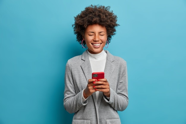 Fröhliche afroamerikanische bloggerin postet bilder online, arbeitet per telefon, lacht über lustige videos im internet, hat spaß und schließt die augen, trägt eine graue jacke,