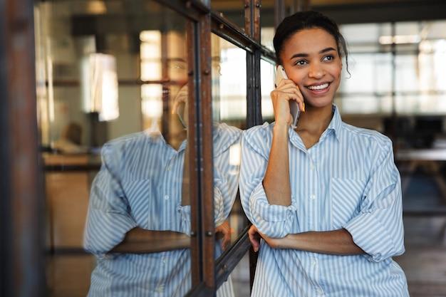 Fröhliche afroamerikanische frau, die am handy spricht und lächelt, während sie sich in einem modernen büro an eine glaswand lehnt