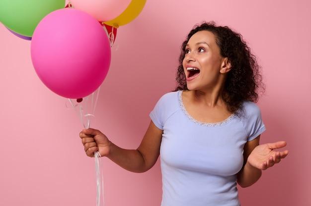 Fröhliche afroamerikanische junge frau in blauem t-shirt posiert vor einem rosafarbenen hintergrund mit bunten, hellen, aufgeblasenen luftbällen in ihren händen und betrachtet sie mit überraschtem gesichtsausdruck.