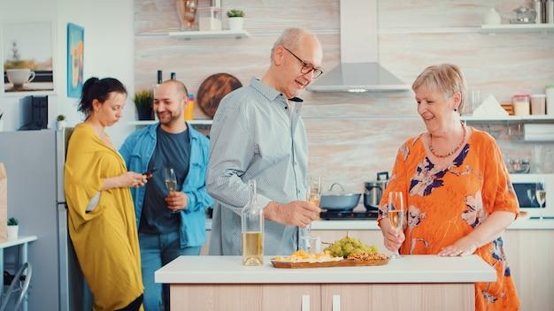 Fröhliche alte ältere erwachsene familie umarmt lachend tanzen und trinken ein glas weißwein vor jungen paaren. in der küche. oma und opa umarmen sich lächelnd und tochter macht ein foto