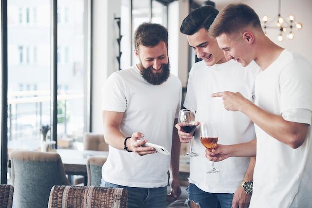 Fröhliche alte freunde kommunizieren miteinander und telefonieren mit einem glas whisky oder wein in der kneipe. konzept von unterhaltung und lifestyle. wifi verband leute in stehtischbesprechung.