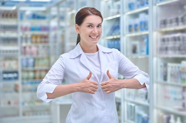 Fröhliche apothekerin, die in der apotheke steht