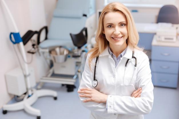 Fröhliche arbeitszeiten. lächelnder, fröhlicher, selbstbewusster gynäkologe, der im gynäkologie-kabinett steht, freude ausdrückt und spaß an der arbeit hat