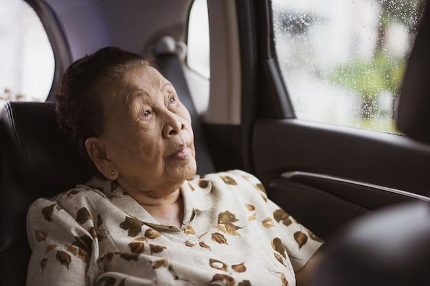 Fröhliche asiatische alte frau, die einen fahrzeugsitz hinten nimmt, frau, die mit dem taxi reist