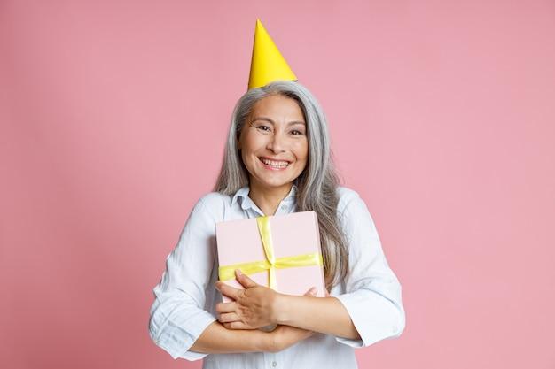Fröhliche asiatische dame mittleren alters mit langen grauen haaren und hellem partyhut hält eine geschenkbox auf rosa hintergrund im studio