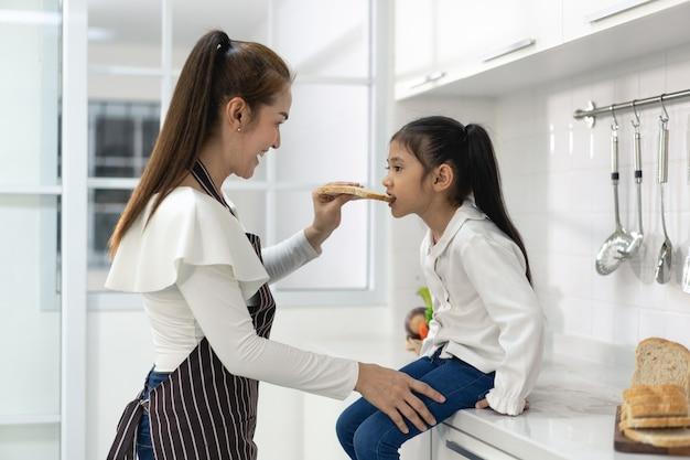Fröhliche asiatische familie mit tochter, die teig beim backen von keksen herstellt, tochter hilft den eltern bei der vorbereitung des backen-familienkonzepts