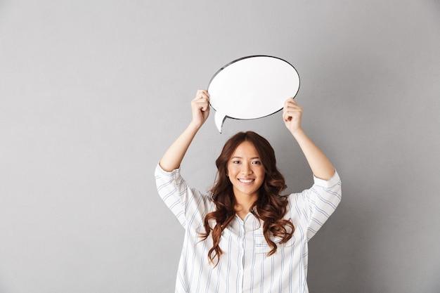 Fröhliche asiatische frau, die isoliert steht und leere sprechblase zeigt