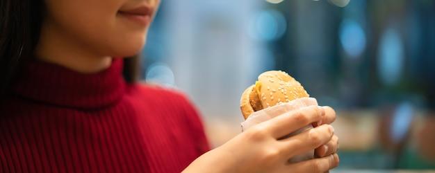 Fröhliche asiatische frau genießen, einen gegrillten fleischhamburger im fast-food-restaurant am abend zu essen