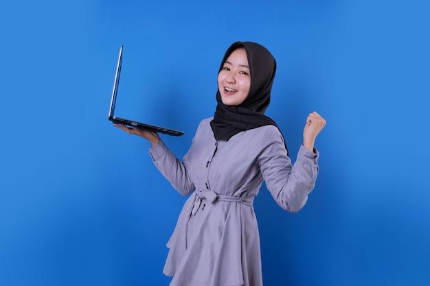 Fröhliche asiatische frau lächeln starken ausdruck bringen einen laptop