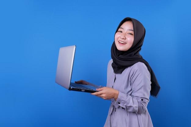 Fröhliche asiatische frau lächeln und bringen einen laptop