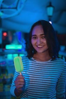 Fröhliche asiatische frau lächelnd, die neoneiscreme im nachtclub hält