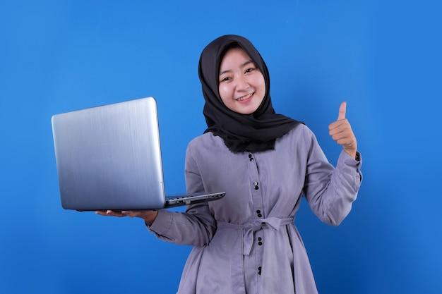 Fröhliche asiatische frau lächelt und bringt einen laptop mit, der mit ihrem daumen okay sagt