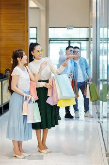 Fröhliche asiatische freundinnen mit vielen einkaufstaschen, die schaufenster mit neuen modischen gegenständen betrachten
