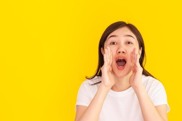 Fröhliche asiatische junge frau schreien - schreien mit der hand hautnah auf gelbem hintergrund des studios. glückliches schönes mädchen, das beim schreien die hand an ihrem reittier benutzt, frau, die lauter spricht. werbekonzept.